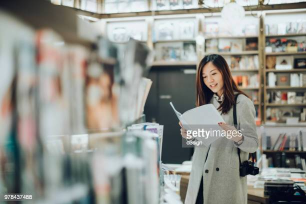 professional female photographer with camera reading books in book store for some inspirations - 雑誌 ストックフォトと画像