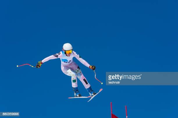 Professional female skier jumping on the red gate during downhill race