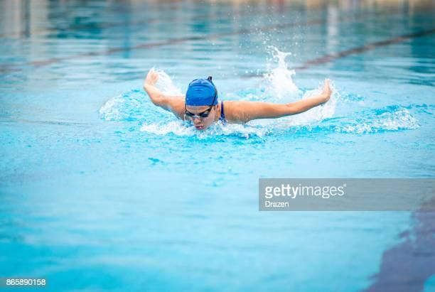 Professional female swimmer swimming butterfly stroke
