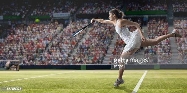 professional female tennis player in mid air serving on grass - serving sport stock pictures, royalty-free photos & images