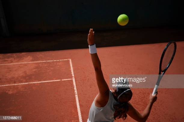 professional female tennis player serving ball during match - tennis stock pictures, royalty-free photos & images