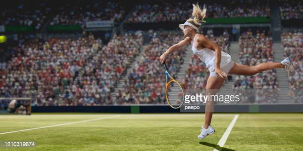 professional female tennis player serving on grass court during match - tennis stock pictures, royalty-free photos & images