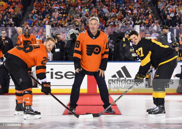 Professional football coach Doug Pederson waits to drop the puck for the ceremonial opening faceoff between Claude Giroux of the Philadelphia Flyers...
