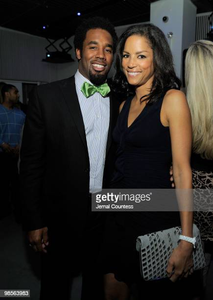 Professional Football Player Dhani Jones and model Veronica Webb pose for a photo at the exclusive viewing party for Dhani Tackles The Globe at Red...