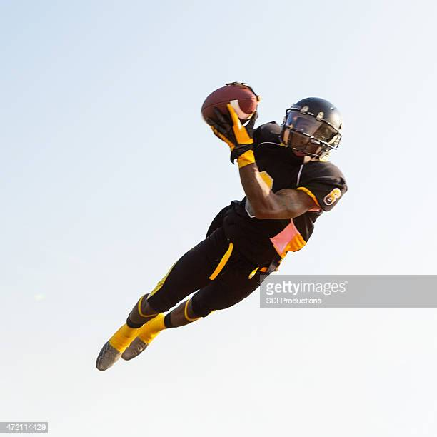 Professional football player jumping to catch ball during game