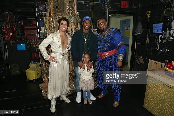 Professional football player Victor Cruz poses for photographs with Adam Jacobs daughter Kennedy Cruz and James Monroe Iglehart after attending...