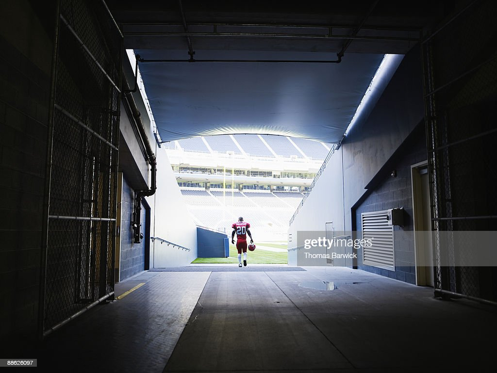 Professional football player walking into stadium : Foto de stock