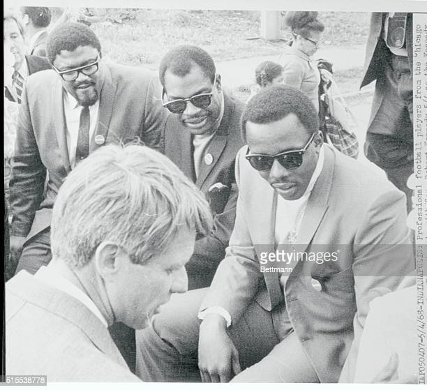 Professional football players from the Chicago Bears and Los Angeles Rams huddle with Sen Robert Kennedy as the Kennedy primary election team tours...