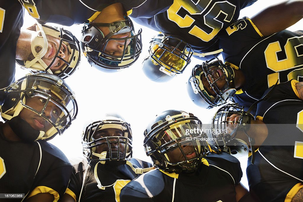 Professional football players huddled while in time out during game : Stock Photo
