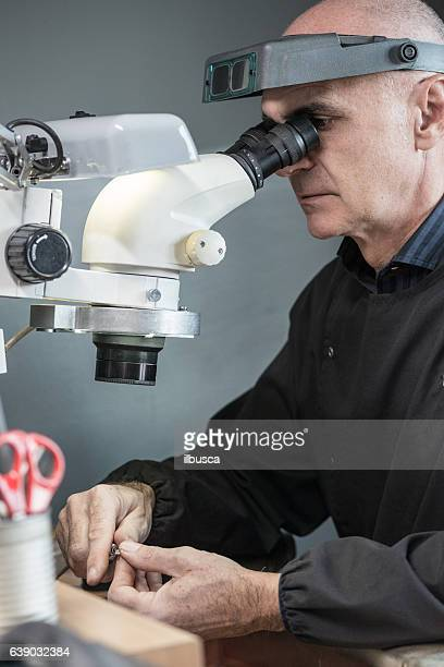 professional gemstone settings jewellery craft laboratory: man working with microscope - jewellery products stock photos and pictures
