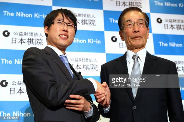 Professional Go player Yuta Iyama shakes hands with his master Kunio Ishii during a press conference as he is given the People's Honor Award by the...