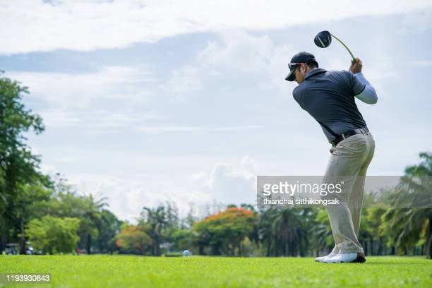 professional golf player is teeing off on green - teeing off stock pictures, royalty-free photos & images