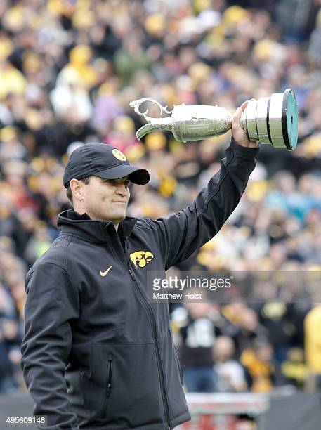 Professional golfer and winner of the British Open Zach Johnson hoists the Claret Cup as he is introduced before the Big Ten matchup between the Iowa...