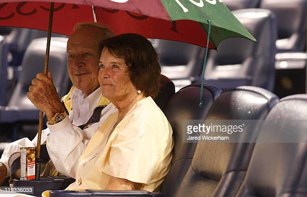 Professional golfer Arnold Palmer a native of Latrobe PA sits under an umbrella with his wife Kathleen Gawthrop during the second rain delay after...
