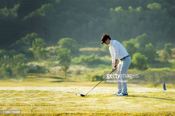 professional golfer asian man approach on the tee off for swing and hitting golf ball and looking fairway in course. hobby in holiday and vacations in sunny morning day on club golf.  lifestyle, and sport concept. - ゴルフクラブ ドライバー ストックフォトと画像
