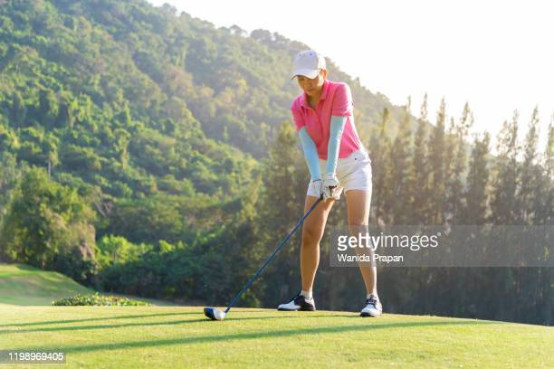 professional golfer asian woman approach on tee off for swing and hitting golf ball and looking fairway in course. hobby holiday and vacations - 女子 ゴルフ ストックフォトと画像