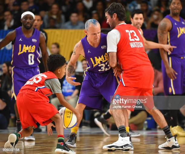 Professional golfer Bubba Watson sets a pick on Flea of the rock band Red Hot Chili Peppers as actor Miles Brown drives to the basket during the 2018...