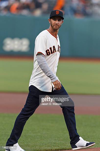 Professional golfer Dustin Johnson walks to the pitchers mound to throw the ceremonial first pitch before the game between the San Francisco Giants...
