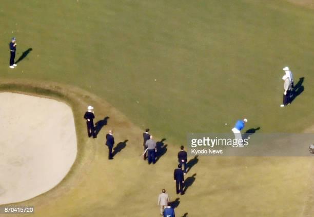 Professional golfer Hideki Matsuyama putts as US President Donald Trump and Japanese Prime Minister Shinzo Abe watch at Kasumigaseki Country Club in...
