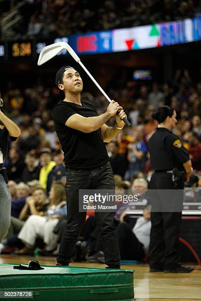 Professional golfer Jason Day hits miniature basketballs into the crowd with an oversize golf club during a timeout in the second half of the game...