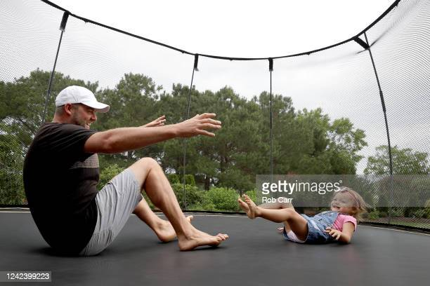 Professional golfer Marc Leishman of Australia plays on the trampoline in his backyard with daughter Eva on June 02, 2020 in Virginia Beach,...