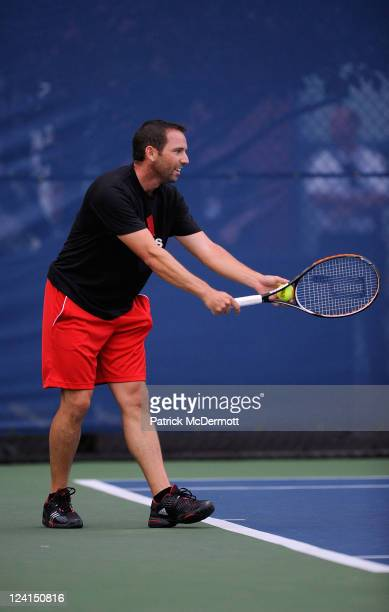 Professional golfer Sergio Garcia serves as he hits ball with Daniela Hantuchova of Slovakia on a practice court during Day Eleven of the 2011 US...