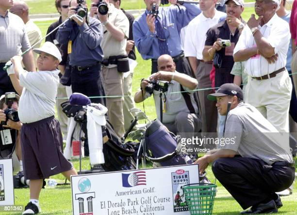 Professional golfer Tiger Woods far right instructs nineyearold junior golfer Darren Saqui April 14 2001 at the CocaCola Tiger Woods Foundation...