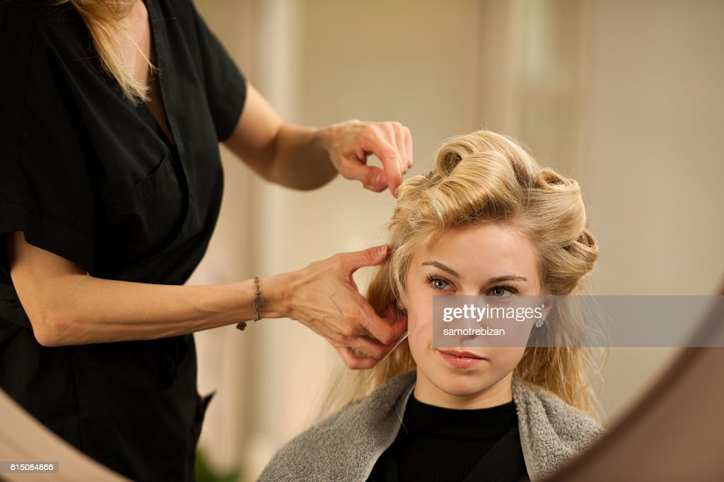 professional hair stylist at work - hairdresser  doing hairstyle : Stock Photo