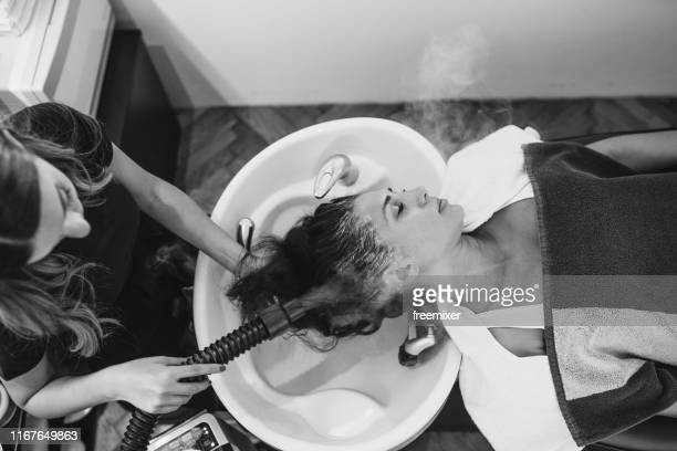 professional hairdresser applying dye on client hair b/w - hair colourant stock pictures, royalty-free photos & images