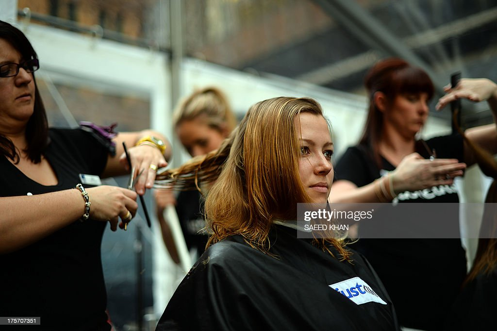 A professional hairdresser gives a free hair cut to a woman in Sydney on August 6, 2013. The Wesley Haircut for homelessness was held at Sydneys Martin Place aimed to break the official world record for the number of haircuts by a team of people in just eight hours. The event was aimed to promote the profile of the issue of homelessness and raise much needed funds for homeless people during Homeless Persons Week . AFP PHOTO / Saeed Khan