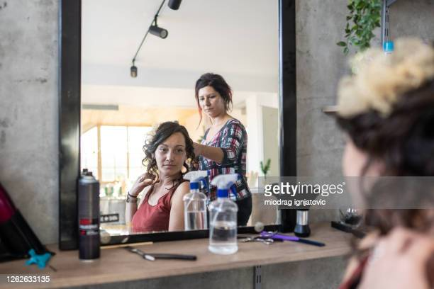 professional hairdresser making elegant hairstyle to young female customer in hair salon - focus on background stock pictures, royalty-free photos & images
