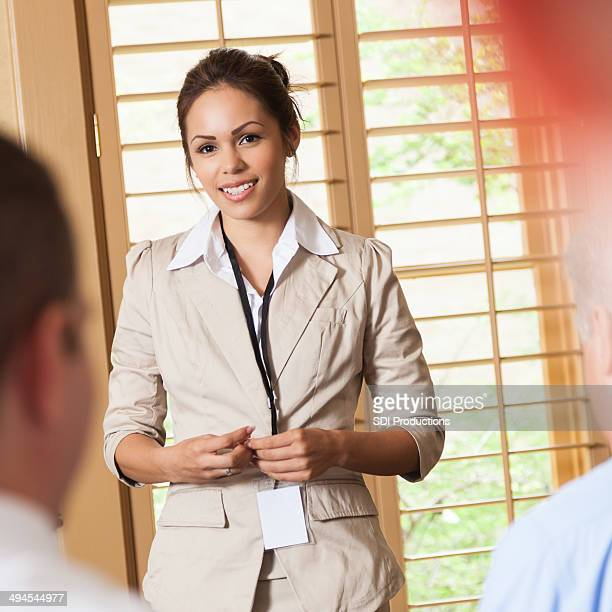 Professional Hispanic woman answering questions during business presentation
