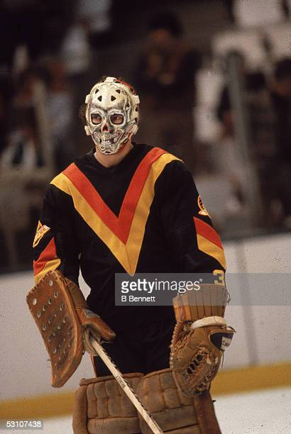Professional hockey player and goalie Gary Bromley of the Vancouver Canucks holds a stick and wears his 'Bones' goalie mask during a road game March...