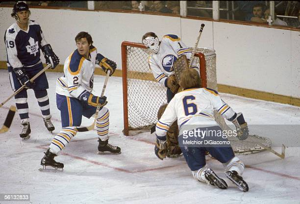 Professional hockey player Tim Horton of the Buffalo Sabres guards his net with fellow defenseman Jim Schoenfeld as Maple Leaf Paul Henderson looks...