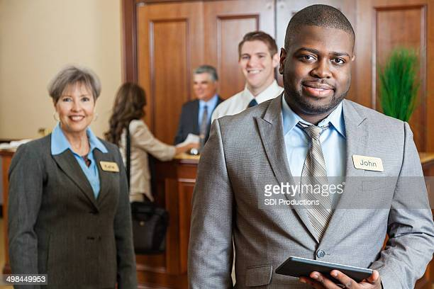 Professional hotel manager standing with staff in lobby