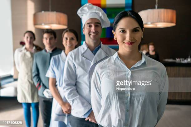 professional hotel staff at a luxury hotel all facing camera smiling standing behind female manager - hotel stock pictures, royalty-free photos & images
