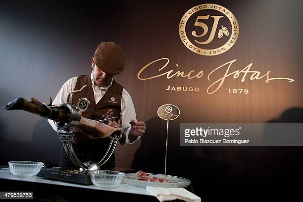 A professional iberico ham cutter cuts slices during the Cinco Jotas International Tapa Award on March 19 2014 in Madrid Spain Twelve finalist from...