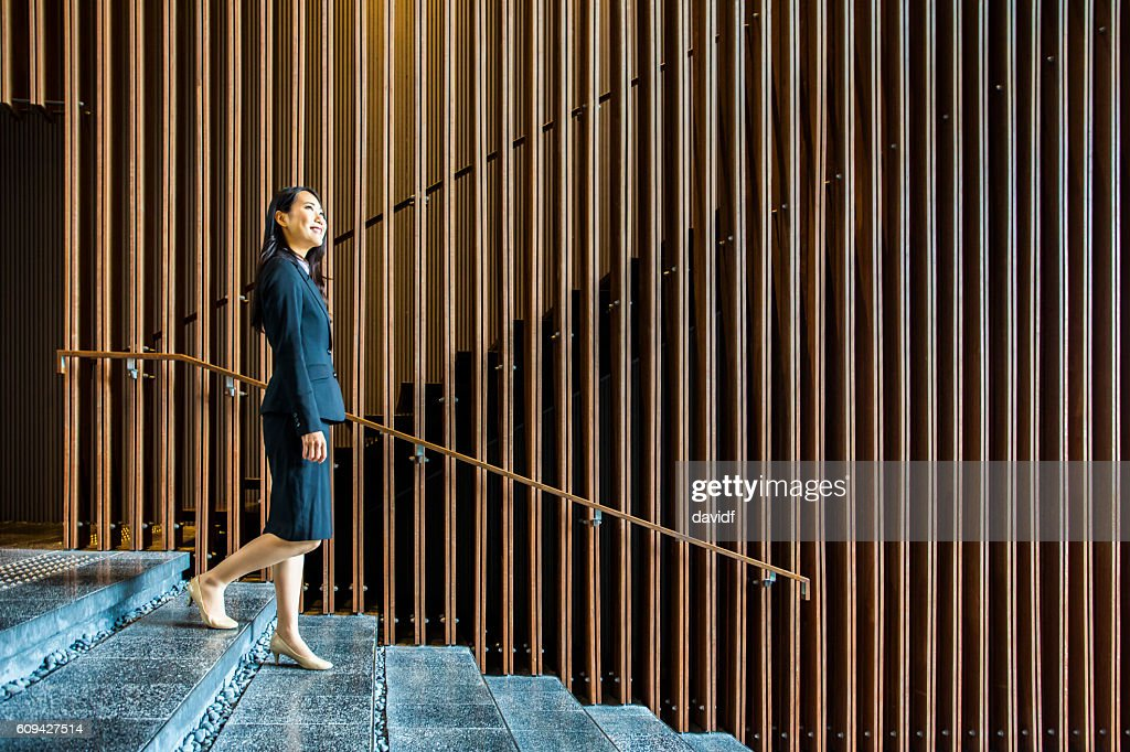 Professional Japanese Businesswoman Walking on Stairs in an Office Lobby : ストックフォト