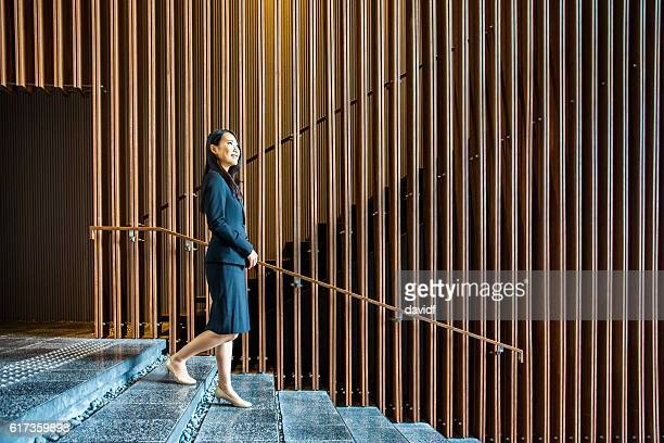Professional Japanese Businesswoman Walking on Stairs in an Office Lobby