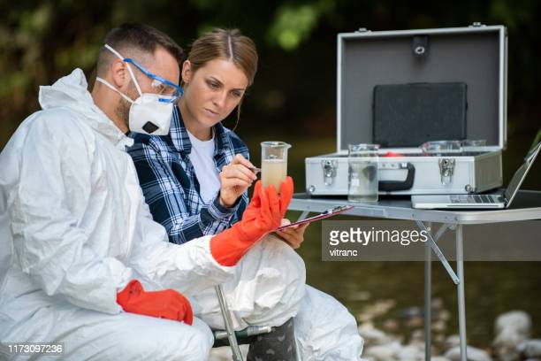 professional laboratory workers  testing water from a forest river - ecologist stock pictures, royalty-free photos & images