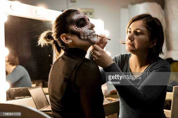 professional make up artist painting face of a woman for halloween night party - performing arts event stock pictures, royalty-free photos & images