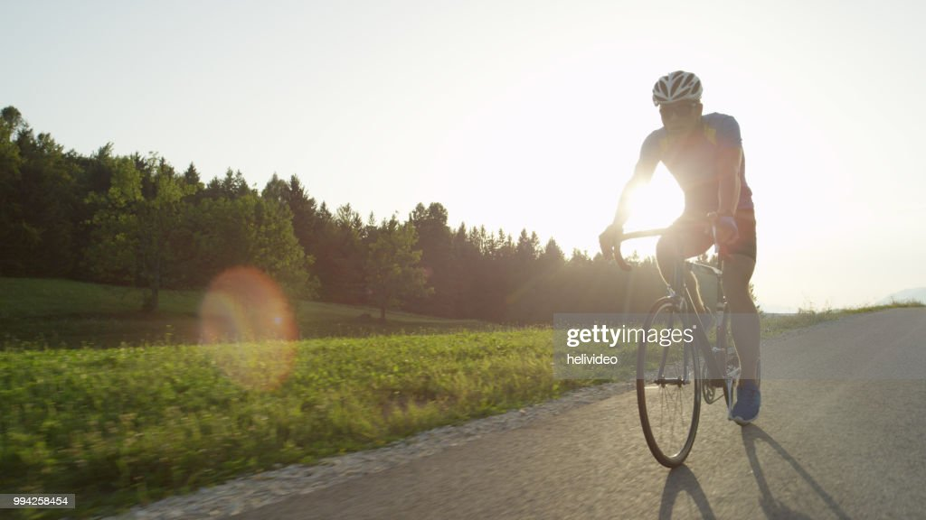 COPY SPACE: Professional male road biker enjoying a sunny cruise on his bicycle. : Stock Photo