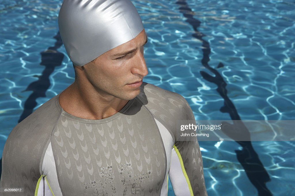 Professional Male Swimmer Looking Sideways Standing in Front of a Swimming Pool : Stock Photo