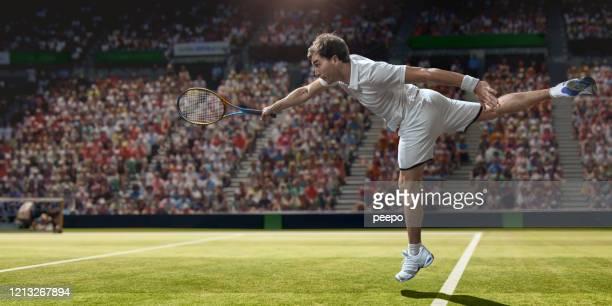 jugador de tenis masculino profesional en el aire sirviendo en hierba - saque deporte fotografías e imágenes de stock