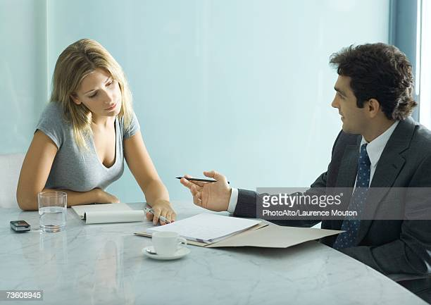 Professional man and woman speaking and looking over document at table
