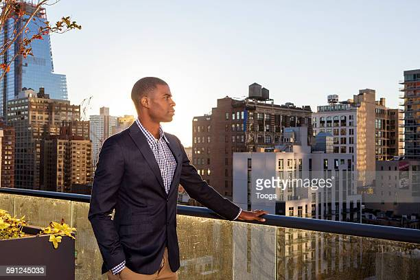 Professional man looking out on city rooftop
