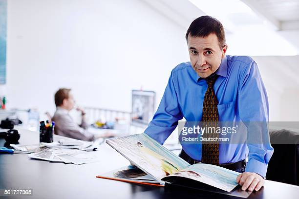A professional man looking through a photo book.