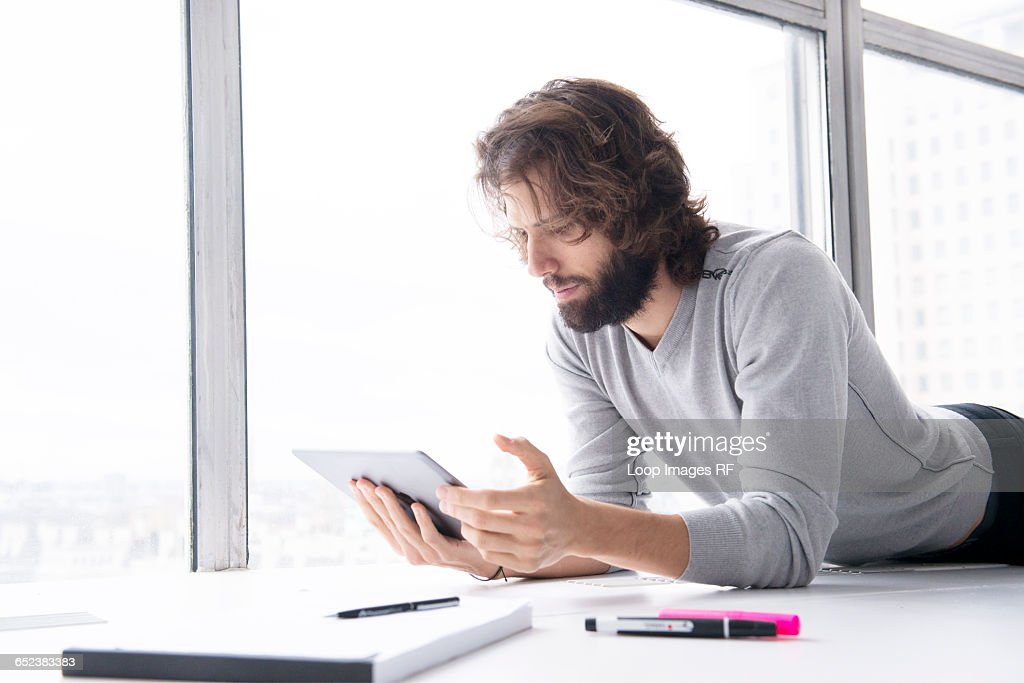A Professional Man Making Notes On A Tablet Computer In A