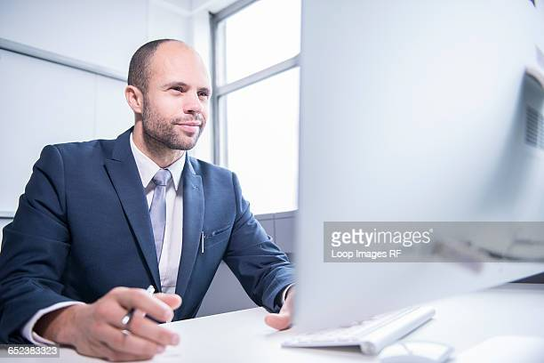 A professional man sitting in front of a computer in an office environment