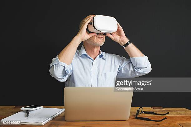 Professional Man Using Virtual Reality Headset Laptop and Smartphone